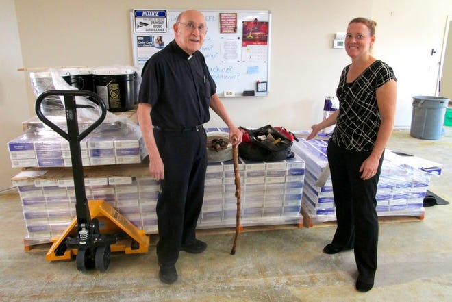 Father Michael Pakula, president of the Geneseo-Atkinson Food Pantry board; and  Nicole Freadhoff, interim director at the Food Pantry, are shown by the stacks of new flooring to be installed in the building after the original flooring was damaged from sewer backup.