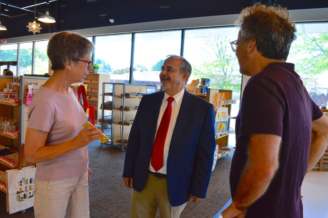 Sue Shapiro, left, shows Rick Morgenstern, center, and Mitch Teplitsky a photo of the information sign that she purchased when the first Morgenstern bookstore closed 25 years ago. On Monday, Shapiro said she wanted to give the sign to Morgenstern for use in the new store.