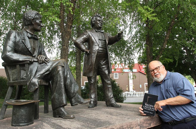 """Edward Finch holds a copy of his book """"Killing Lincolns"""" as he stands next to the Abraham Lincoln and Stephen A. Douglas statues in Debate Square on July 21, 2021, in downtown Freeport."""