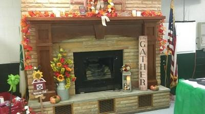 The stone fireplace is one of the attractive features inside the 4-H Activity Center at the Monroe County Fairgrounds. Here it is decorated for one of the annual spaghetti dinners and auctions held before Thanksgiving.