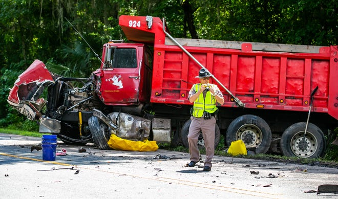 Florida Highway Patrol Cpl. Brett Detweiler takes pictures at the scene of a fatal crash Tuesday morning on Northwest 70th Avenue Road about a quarter of a mile west of the Northwest 72nd Court intersection. A dump truck and a pickup truck collided. The driver of the pickup truck was killed; the dump truck driver was transported to a local hospital.