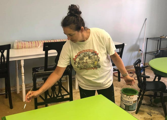 Dr. Debi Graves paints a table in her new artisan studio Alma Bella Academy in Chester, Va. on July 1, 2021.