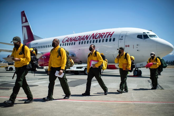 Firefighters from Mexico walk across the tarmac after arriving in British Columbia, Canada, to assist in fighting wildfires there.