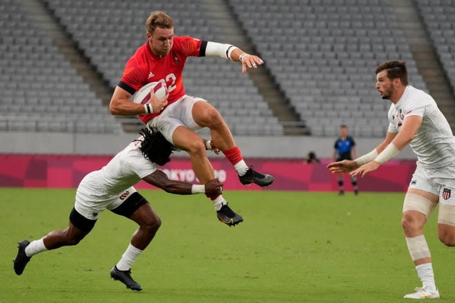 Britain's Harry Glover leaps, being tackled by Carlin Isles of the United States during their men's rugby sevens quarterfinal match against the U.S. at the 2020 Summer Olympics, Tuesday, July 27, 2021, in Tokyo. (AP Photo/Shuji Kajiyama)