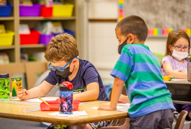 Moses Rieman, 5, left, and Paetyn Rasing, 5, wear masks while doing classwork during a pre-K summer program in July at Swanson Traditional School in South Bend.