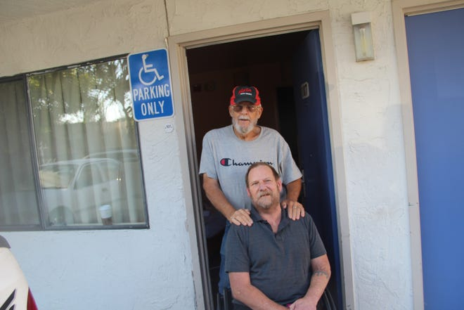 Randy Gibbons stands behind Richard Koehler at the Motel 6 in Yreka. Gibbons is renovating an RV so Koehler can return home to Happy Camp following the Slater Fire