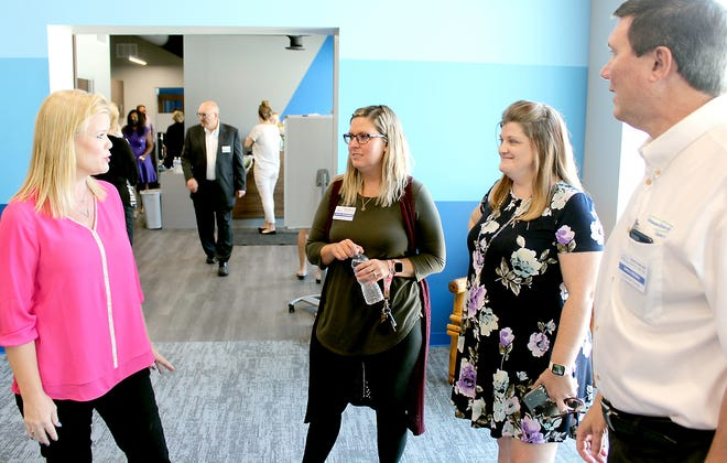 Christy Trammell, president and CEO of Three Rivers Chamber of Commerce, explains a few details about the chamber's new location to Alicia Finnerman, Amanda Kindig and Greg Moore at an open house Monday, marking the opening of the Chamber's new location.