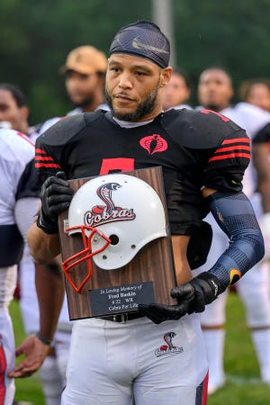 Keilen Mcdonald holds the Cobra Hall of Fame induction plaque honoring the late Fred Baskin.