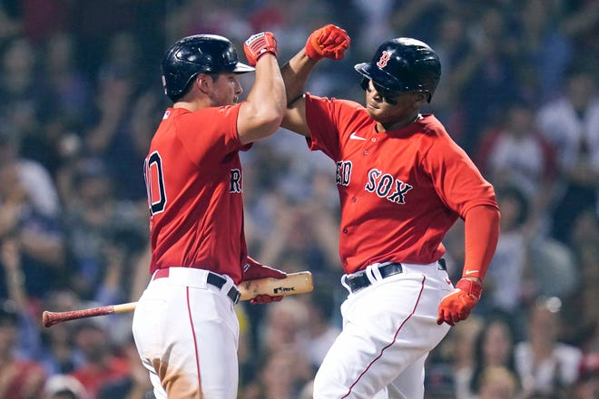 Boston Red Sox's Rafael Devers, right, is congratulated by Hunter Renfroe after his solo home run during the Red Sox's 5-4 win against the Toronto Blue Jays at Fenway Park.
