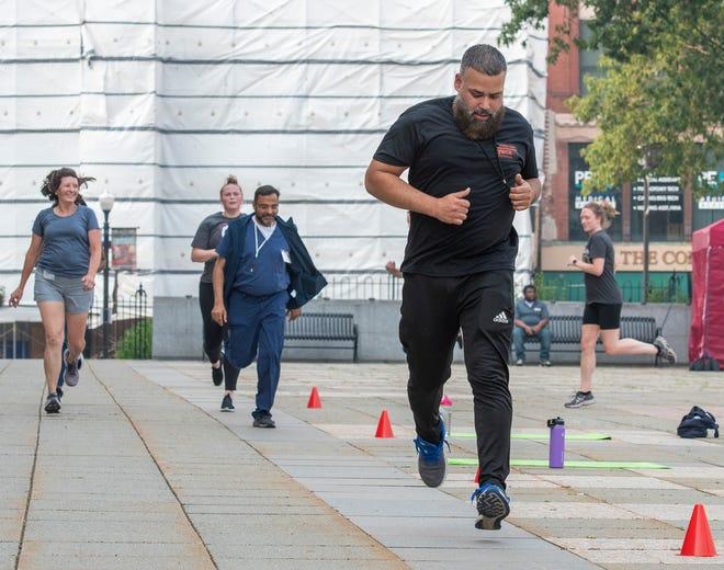 Trainer Rolando Cruz leads a warm-up jog Monday on Worcester Common.
