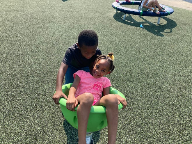 Sanyaih Custis was coaxed into a playground spinner by her brother Sincere.