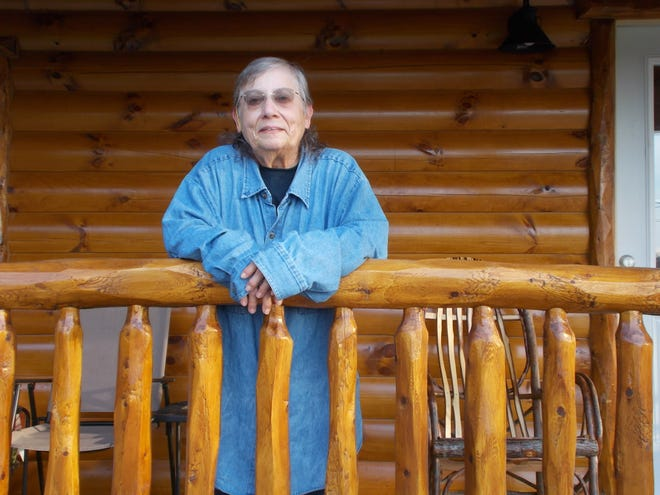 Christine Bell stands on the porch of her new cabin on Clyde-Green Springs Road.