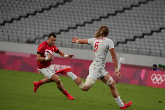 Britain's Alex Davis, left, gets past Joe Schroeder of the United States to score a try, in their men's rugby sevens quarterfinal match at the 2020 Summer Olympics, Tuesday, July 27, 2021 in Tokyo, Japan. (AP Photo/Shuji Kajiyama)