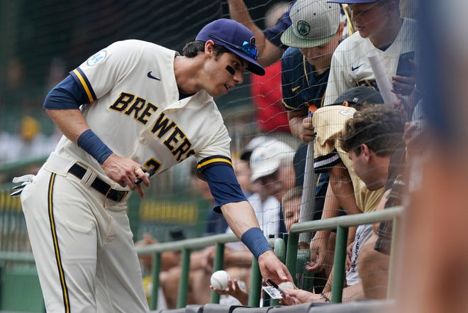 Left player Christian Yelich signs autographs for fans prior the match final week.  He has tested positive for COVID-19.