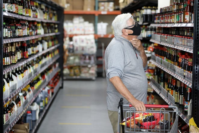 A customer looks at the selection of sauces at Kam Man Market. Monday, July 26, 2021