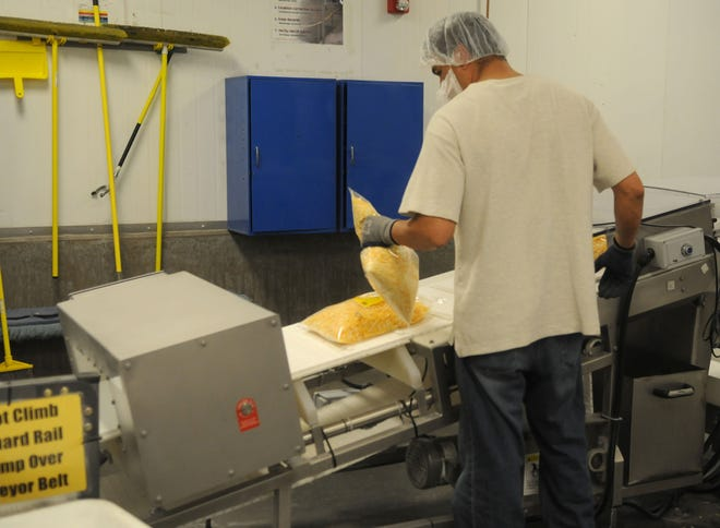 A Pacific Cheese employee checks a bag of cheese coming off the conveyor belt.