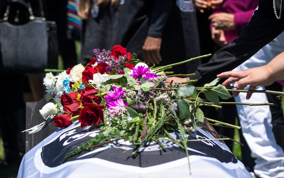 Friends and family put dozens of flowers on the coffin of Julian Gallegos, 30, during his funeral ceremony on Tuesday, July 20, 2021.