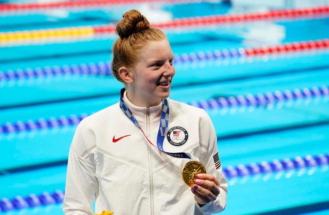 Lydia Jacoby holdsup her gold medal after winning the women's 100-meter breaststroke.