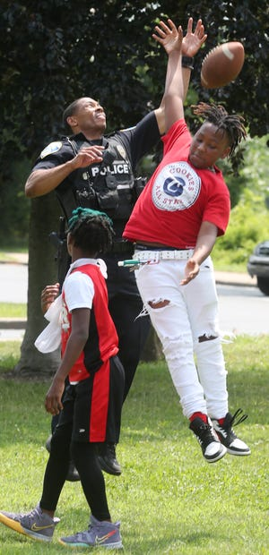 Akron police officer Trumaine Riley and Jermaine Manuel, 13, try to catch a football as Corey Balark, 11, watches during the Akron Police Department's CommUnity outreach event Wednesday at Summit Lake Community Center in Akron. The event included games, free ice cream, hotdogs and refreshments for the kids.