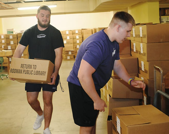 Members of the University of Mount Union football team, from left, offensive lineman Carson Barrett and tight end PJ Morris, move some of the 800 boxes of books in the basement of Rodman Public Library on Tuesday, July 27, 2021.