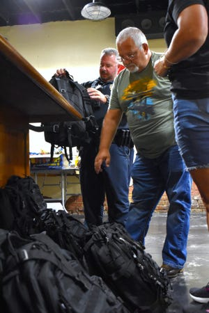 Law enforcement officers pick up backpacks with gear at Mill Street Garage Wednesday, July 28, 2021. Heroes with Hope used a recent donation to provide the bags and lunch to 75 officers from across Carter County law enforcement agencies.