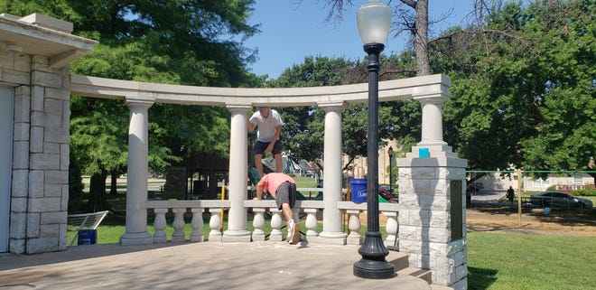 Workers clean and repair the pergola at Central Park. Vandals damaged several balusters earlier this year.