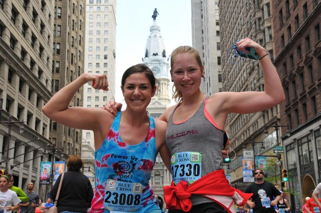 Two happy runners pose near Philadelphia's City Hall on their way to the finish line in the Broad Street Run 10-Miler.