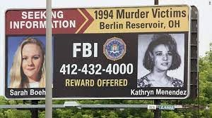A billboard advertises an FBI reward for murder victims Sarah Boehm and Kathryn Menendez, whose bodies were both found in a wooded area in Deerfield.