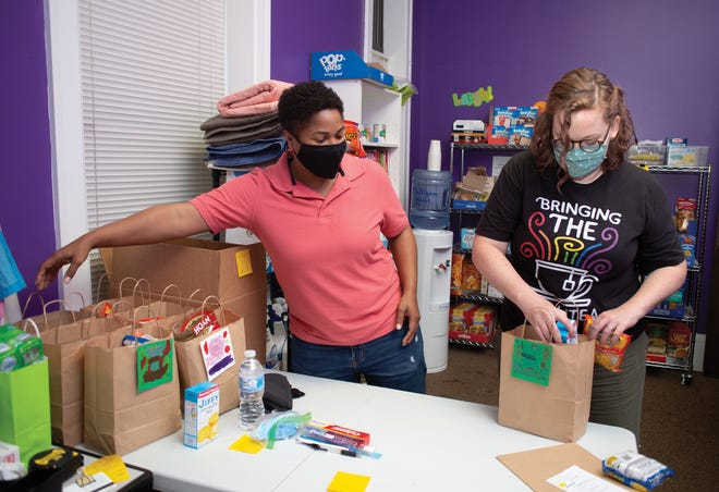 Karen Hewitt, deputy director of Kaleidoscope Youth Center, and Amanda Erickson, director of education and outreach, pack to-go resource bags.