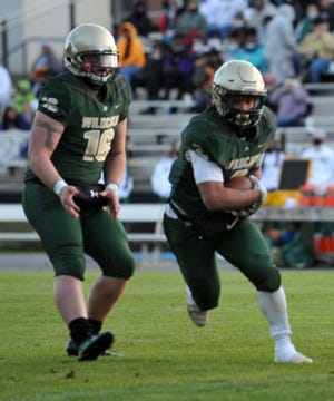Eastern Randolph's Na'Hiem Lilly (right) runs after taking the handoff from quarterback Stratton Barwick in the spring 2021 season. [Mike Duprez/Courier-Tribune]