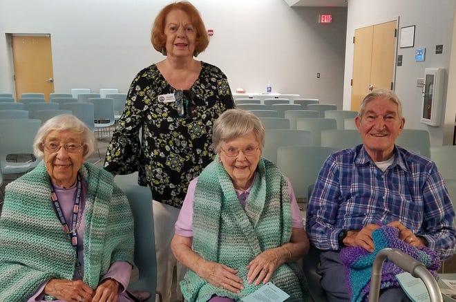 Sacred Heart Parish Ladies' Guild knitter Maggie DiRocco, standing, presented hand-knit prayer shawls to World War II veterans, from left, Dorothy Managan, Myrl Jean Hughes and George Sarros.