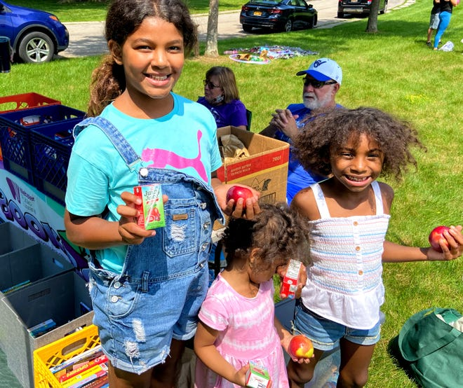 BookBox attendees show off the apples and juice boxes they receive when coming to the Webster Public Library mobile library service in Phillips Village, thanks to weekly donations from Hegedorns Market.