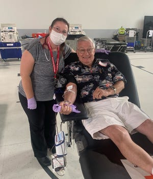 Amy Wood, a phlebotomist for the American Red Cross in Toledo, assists Pat Leibold of Monroe with donating a pint of blood at a blood drive held Tuesday in the newly remodeled gym at St. Michael Catholic Grade School in Monroe.  Leibold was one of more than 50 persons who gave blood during the six-hour drive.