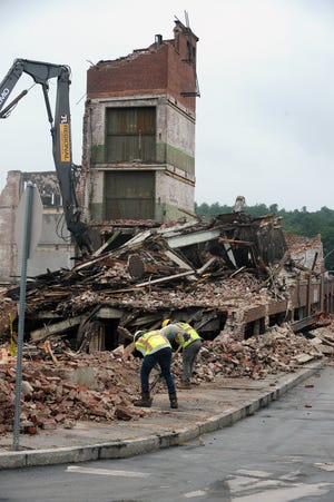 Workers clear bricks and debris from the Draper Corp. mill building on Freedom Street, July 28, 2021.