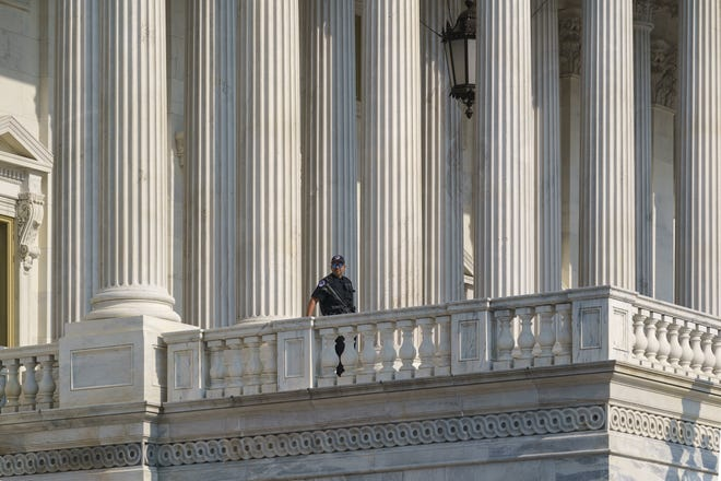 A U.S. Capitol Police officer keeps watch at the House of Representatives early Wednesday, July 28, 2021, at the Capitol in Washington. The Senate is pursuing a funding bill to relieve the depleted budget of the Capitol Police in the following the Jan. 6 insurrection and the inauguration of President Joe Biden.