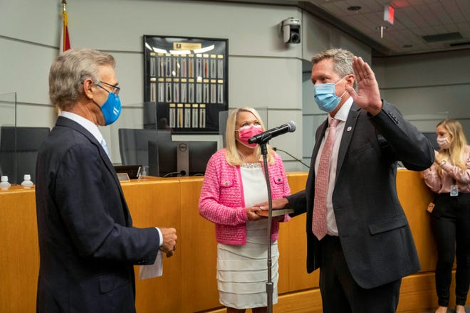 Mike Burke  is sworn in as the new Palm Beach County Superintendent of Schools with his hand on the bible with his wife Kristin officiated by chairman Frank Barbieri on July 28, 2021. in West Palm Beach.