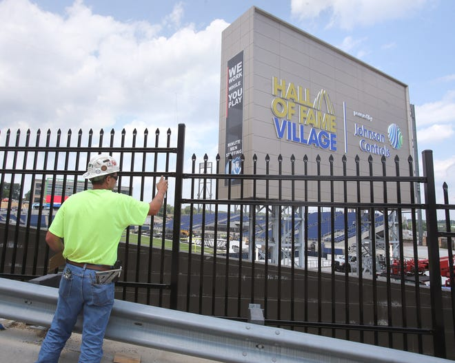 Mike Goodrick, who works for Great Northern Fence Co. based in Portage County, touches up paint at Tom Benson Hall of Fame Stadium, a key piece of the Hall of Fame Village powered by Johnson Controls in Canton. A new scoreboard has been installed on a plaza at the end of the stadium.