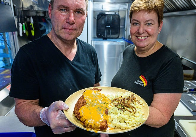 Guido and Daniela Kramp, owners of the German Street Food food truck, hold a plate of their Rahm schnitzel.