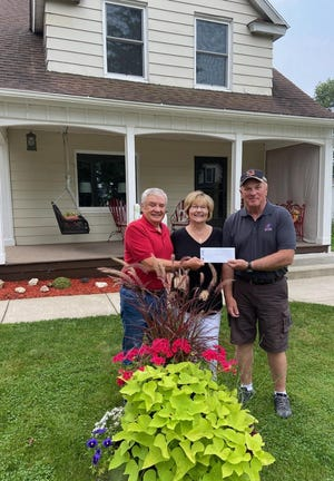 Mike Jones of Arrow Real Estate presents one of the summer pride in ownership awards to Jim and Ann Herriot, 1011 W. Prospect St. For over 30 years Arrow Real Estate has been presenting the pride awards. The award is given to homeowners who take particular pride in their home. Nominations for the award are submitted by community residents.
