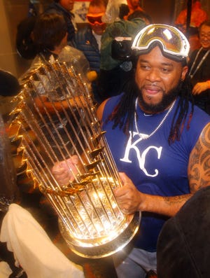 Then-Kansas City Royals starting pitcher Johnny Cueto holds the Commissioners Trophy in the clubhouse after defeating the New York Mets to win Game 5 of the World Series at Citi Field in New York. Cueto was acquired by the Royals in a trade-deadline deal that helped bolster a Royals team that was already 20 games above .500.