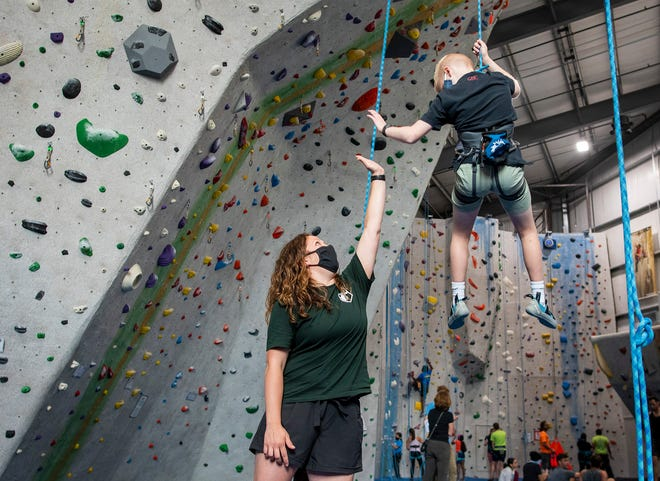Climbing coach Kendra Warhol high-fives a young climber after the boy made it to the top of a wall and is being lowered to the floor at the Central Rock Gym Wednesday.