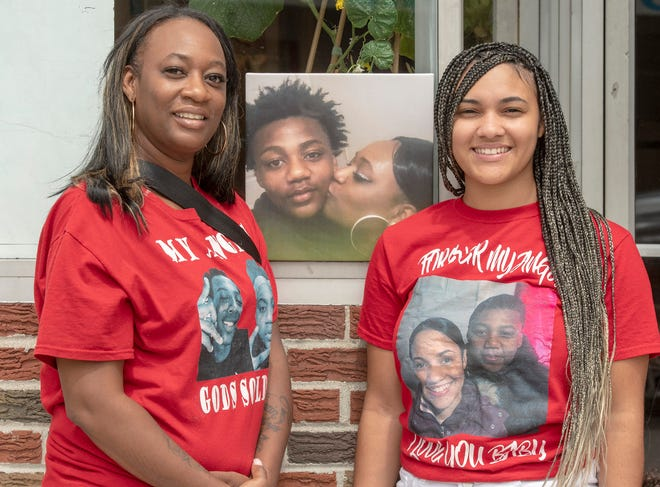 Jamilla Carlor, left, and her daughter, Jaliah, stand in front of a portrait of their son and brother, Dante. The women have organized a basketball tournament in his honor.