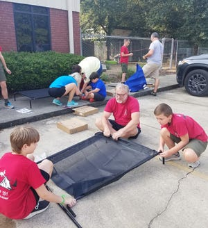 Members of Boy Scout Troop 151 from Southside, along with parents and siblings, help assemble dog beds July 24 at the Humane Society Pet Rescue and Adoption Center in Gadsden.