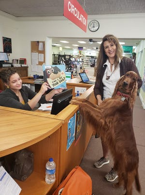 """Gabrielle Demay of the Van Alstyne Library staff offers a dog book to author Dawn Secord and her star dog Bling."""""""