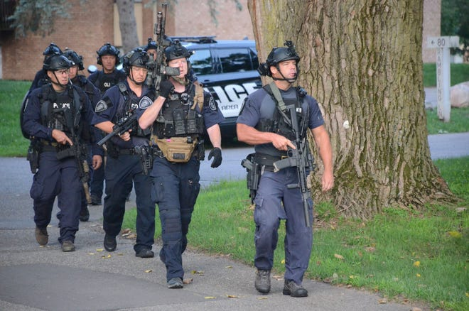 Members of the Battle Creek Police Department Emergency Response Team prepare to search an apartment building for a possible suspect following a shooting Wednesday morning.  (Trace Christenson/The Enquirer)