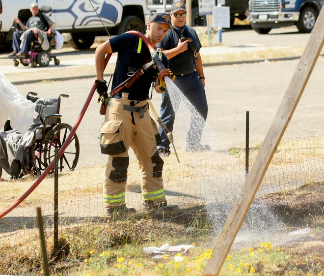 Bremerton Fire Department's Lt. Jeremy Dixon sprays down the grass at the scene of a small brush fire on MLK Way in downtown Bremerton on July 27.