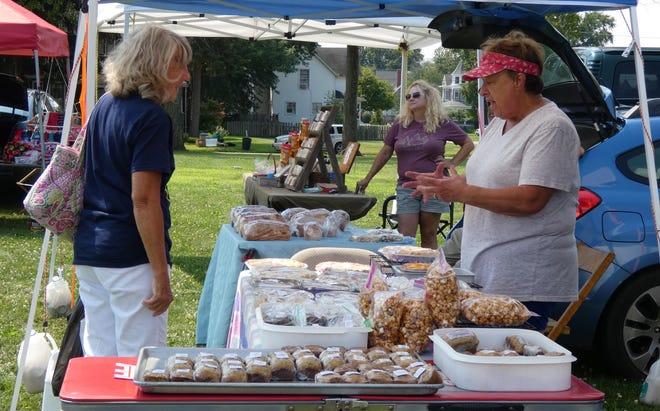 Marci Teynor (right) speaks with shopperCheryl Swihart on at the Crestline Farmers Market.