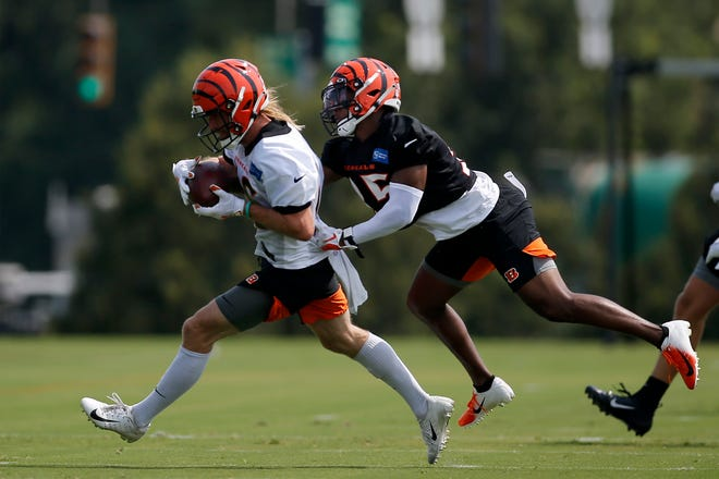 Cincinnati Bengals wide receiver Trenton Irwin (16) runs with a catch as he's brought down by Cincinnati Bengals cornerback Jalen Davis (35) during the first day of training camp practices at the Paul Brown Stadium practice facility in downtown Cincinnati on Wednesday, July 28, 2021.