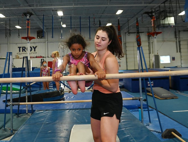 Sariya Tejani, 7, works on the single bar with the help of coach Caity Buechner, 23, during practice at Troy Gym.