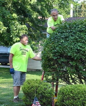 Deke Lueke steadies the ladder while Rich Harman trims bushes at Ron and Liz Cashen's home. Nearby, several teens were weeding and mulching around the home. Harman has headed the teen work crew for eight years, and this year, Lueke has stepped in to help on bigger jobs.